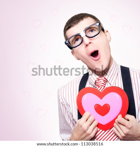 Funny Portrait Of A Romantic Nerd Dreaming Of A Long Lost Love His Dorky Heart Still Aches For, On Pink Heart Shaped Background - stock photo