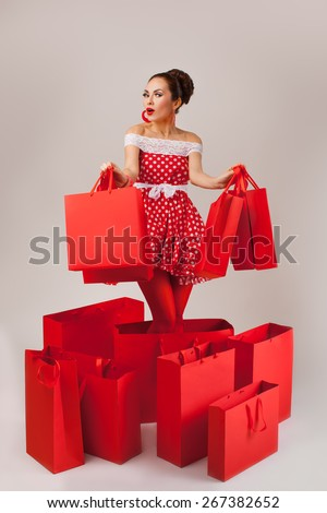 Funny portrait of a surprised cute young female model holding many shopping bags in her arms wearing red dress - stock photo