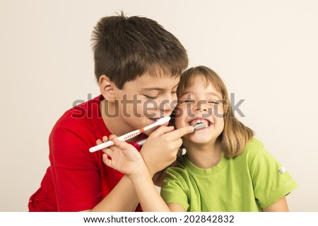 Funny portrait of a young girl and a young boy brushing each other  - stock photo