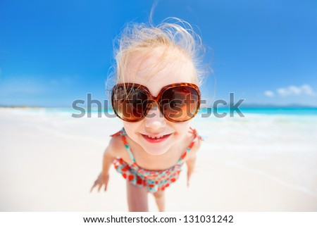 Funny portrait of adorable little girl at tropical beach