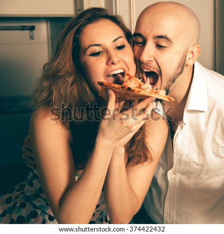Funny portrait of beauty couple with pizza. Celebrate, disco, party, nightlife, entertainment, friendship concept. - stock photo