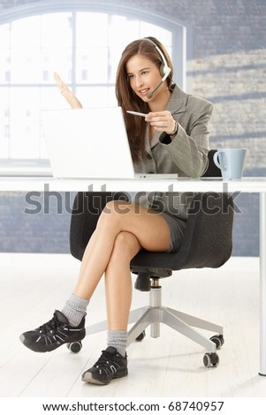 Funny portrait of call center operator girl working at desk, sitting in smart top but in comfortable shoes under table.?