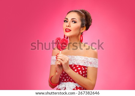 Funny portrait of cute young female model with candy in her arms wearing red dress - stock photo