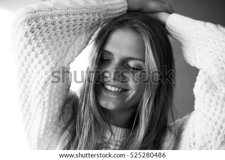 Funny portrait of fashionable model with long blonde hair in white sweater. Beautiful face with freckles. White shiny smile. Hipster style. Daylight. Close up. Monochrome studio shot