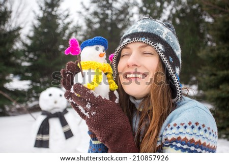 Funny portrait of winter girl with little snowman. soft daylight. focus on woman - stock photo
