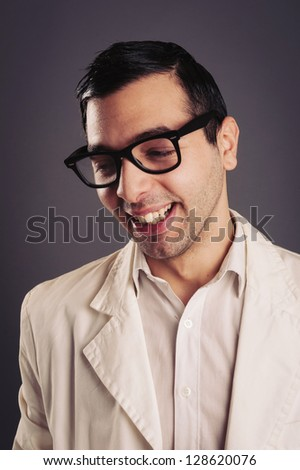 Funny portrait of young nerd with eyeglasses on grey background. - stock photo