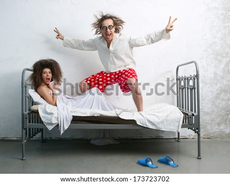 Funny pranks of man and woman in the bed - stock photo