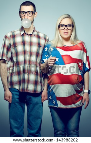 Funny pregnancy concept: portrait of two hipsters (husband and wife) in trendy glasses and clothes playing with their bubble gums. Studio shot - stock photo