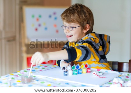 Funny preschool kid boy with glasses having fun with coloring. Little child drawing with colorful watercolors and gouache, indoors. School, education concept - stock photo