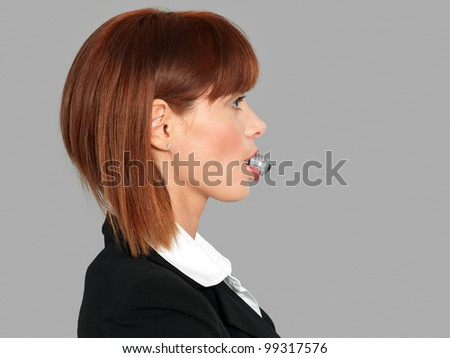 funny profile portrait of a beautiful, young businesswoman, with a light bulb in her mouth, on gray background