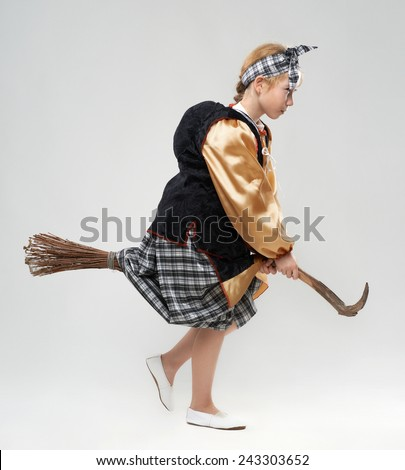 funny redhead girl in witch costume flying on a broomstick - stock photo