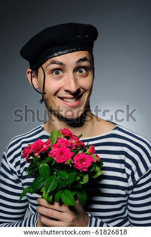 Funny romantic sailor man holding rose flowers prepared for a date - stock photo