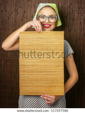 Funny rural woman cook holdin ledle and chopping shim, space for your text - stock photo