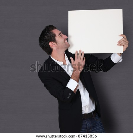 Funny salesman holding whiteboard - stock photo