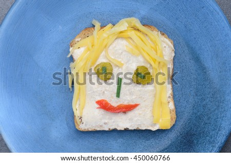 funny sandwich for children  on blue plate - stock photo