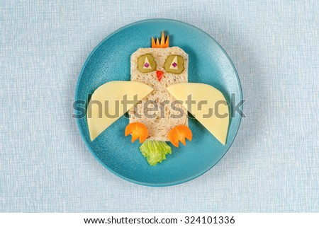 Funny sandwich owl for kids on plate, healthy breakfast for Easter. Isolated on blue - stock photo