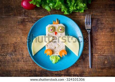 Funny sandwich owl for kids on plate, healthy breakfast. Wooden table background,  - stock photo