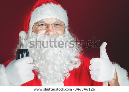 Funny Santa Claus holding Cola fresh beverage at glass bottle. Christmas holiday, New Year. Thumb up gesture. Copy space for design, text at red background