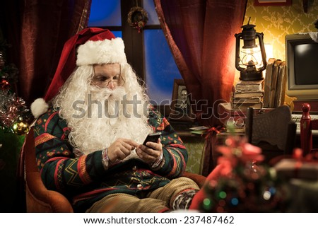 Funny Santa Claus using his new smartphone and relaxing at home - stock photo