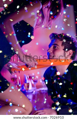 Funny scene of young happy playfully couple at celebration - stock photo