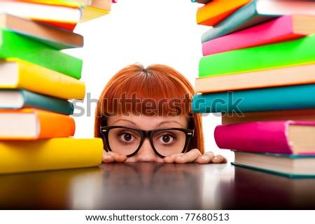 funny schoolgirl peeking behind books and desk, isolated on white - stock photo