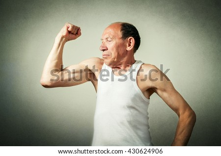 funny senior man showing the muscles