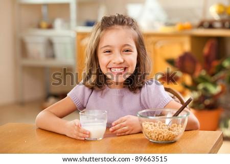 funny shot of a little girl having breakfast: milk mustache - stock photo