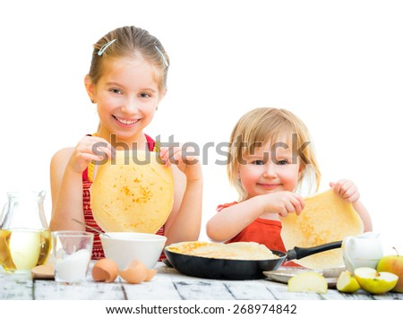funny sisters cooking pancakes on kitchen, white background - stock photo