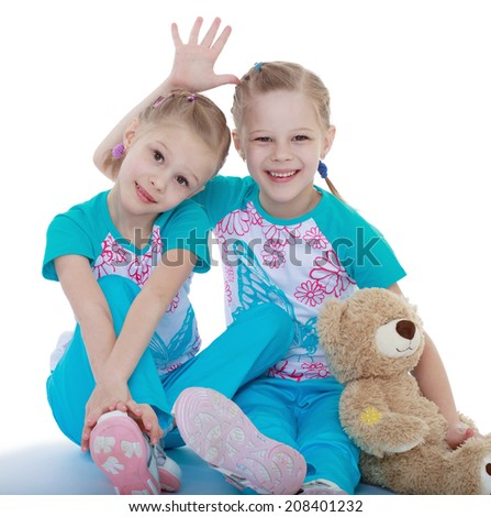 funny sisters with a teddy bear on a white background.kindergarten, the concept of childhood and joy, teens - stock photo
