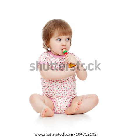 Funny sitting baby  with musical toy. Isolated on white background - stock photo