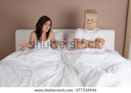 Funny situation in bed. Young couple lying in bed and man with paper bag over head - stock photo