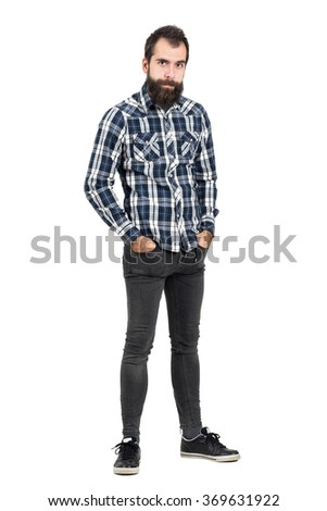 Funny skeptical expression of bearded hipster with hands in pockets looking at camera. Full body length portrait isolated over white studio background.