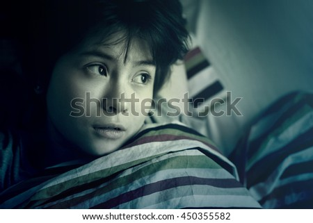 Funny sleepy girl teenager lying in bed under a striped colored blanket. Toned