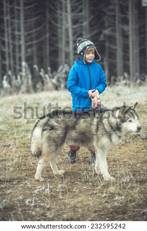 Funny small boy with his dog walking in autumn forest. motion, toned image - stock photo