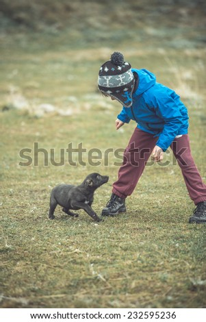 Funny small boy with his dog walking in autumn forest. motion, toned image, vignette, focus on head boy - stock photo