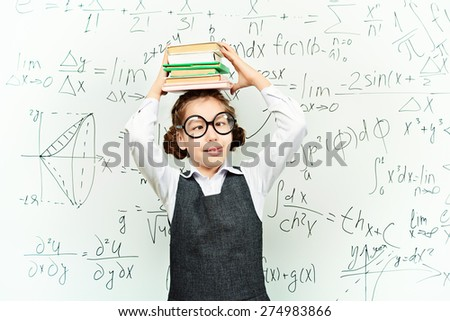 Funny smart schoolgirl in big glasses stands with books at the blackboard. Education. - stock photo