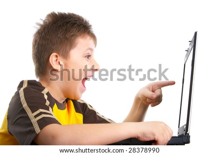 Funny smiling boy working with laptop. Isolated over white background - stock photo