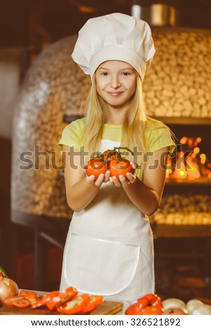 Funny smiling chef girl holding tomatoes at restaurant kitchen - stock photo