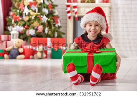 Funny smiling child in Santa red hat holding Christmas gift in hand.  - stock photo