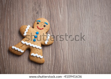 Funny smiling gingerbread man on wooden table. Smiling eatable character with good taste. Close up macro, copy space on dark brown wood - stock photo