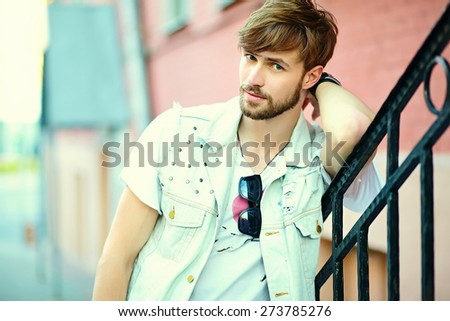 Funny smiling hipster handsome man guy in stylish summer cloth in the street in sunglasses - stock photo