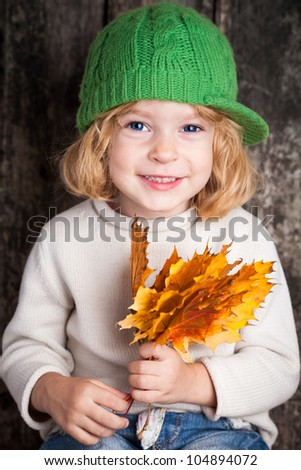 Funny smiling kid holding yellow maple leaves. Autumn concept - stock photo