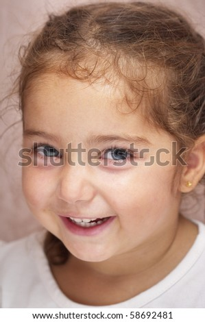 Funny smiling little girl portrait over defocused background