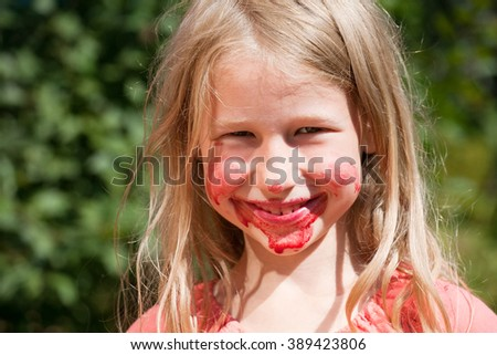 funny smiling little girl with red juice on cheeks and chin - stock photo