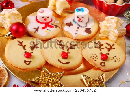funny snowman and reindeer shaped christmas cookies made by kids - stock photo