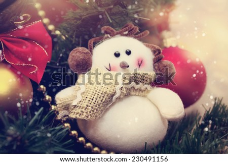 Funny snowman decoration in scarf on Christmas tree background - stock photo