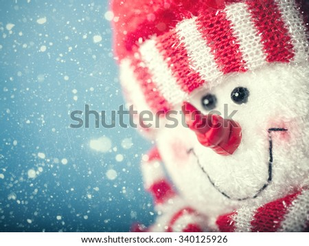 Funny snowman portrait against snowfall, abstract christmas backgrounds - stock photo