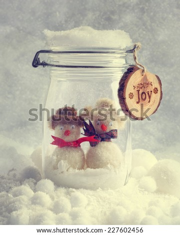 Funny snowmen in glass jar with Christmas ribbons - stock photo