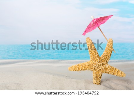 Funny starfish holding a pink parasol on the beach