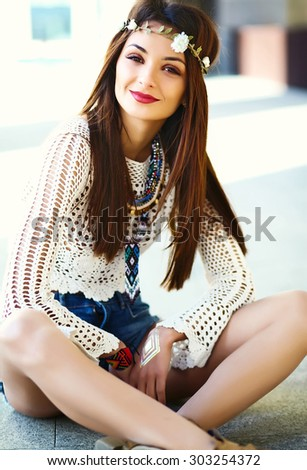 Funny stylish sexy smiling beautiful young hippie woman model in summer bright hipster clothes dress in the street in hat - stock photo